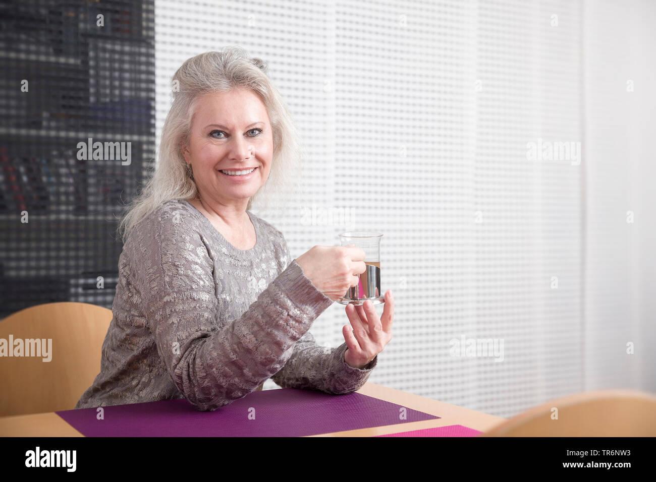 Contenido senior femenino sentado al escritorio en el salón y beber té, Alemania Imagen De Stock
