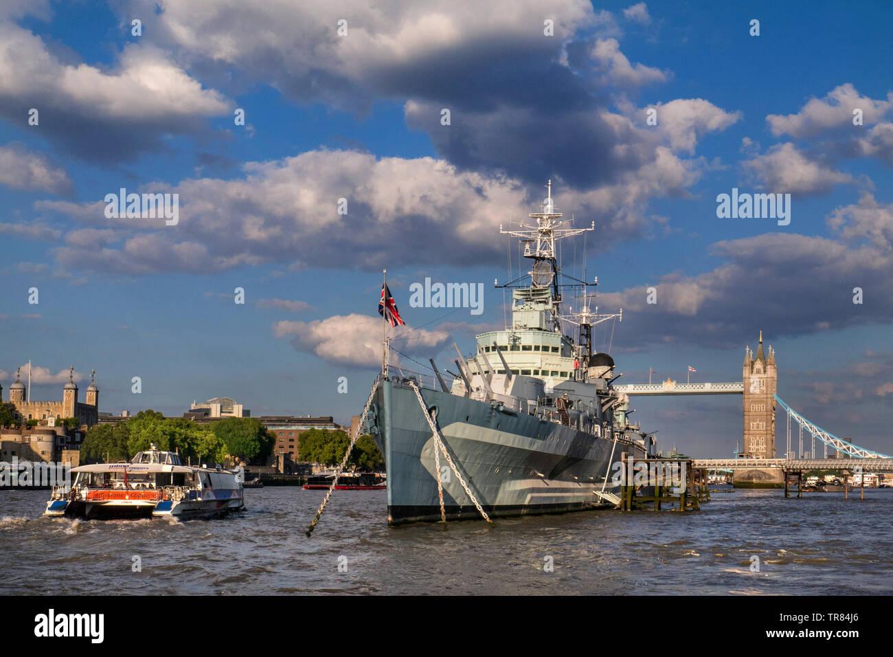 HMS Belfast museo barco anclado en el río Támesis, con la Torre de Londres, a un paso del río RB1 Clipper Barco y el Puente de la torre detrás de London SE1 Foto de stock