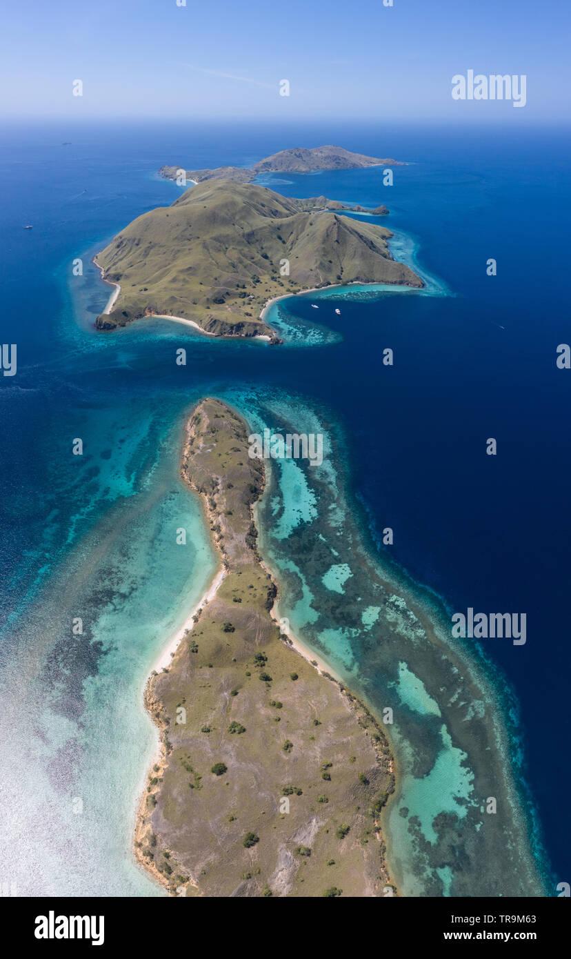 Visto desde una vista de pájaro, las islas tropicales en el Parque Nacional de Komodo, en Indonesia, están bordeadas por increíbles, biodiversidad de los arrecifes de coral. Foto de stock