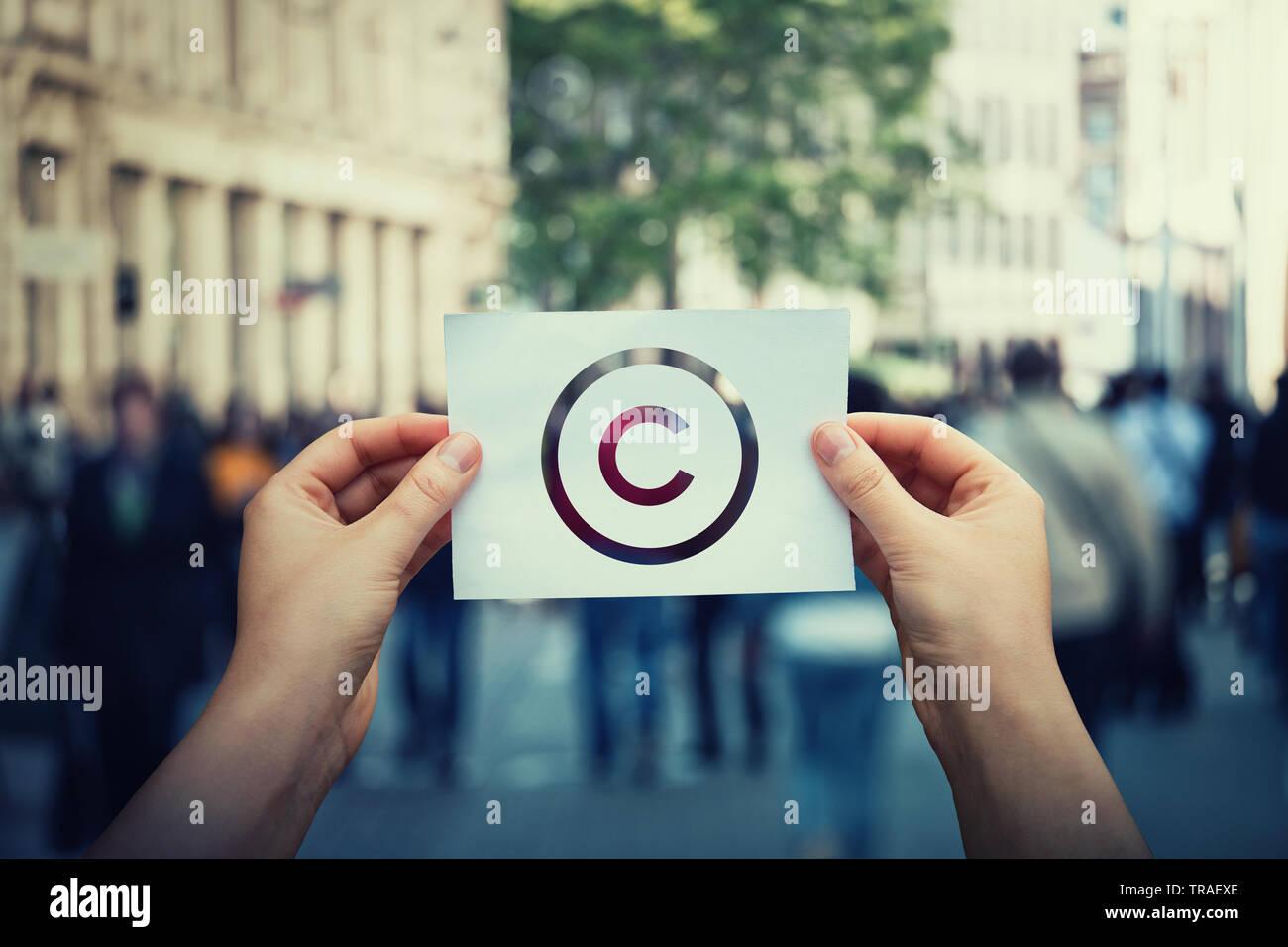 Manos sostienen el papel con el símbolo de copyright. Derechos legales internacionales signo de propiedad intelectual, la protección de patentes. Copyleft licencia de marca. Creación Foto de stock
