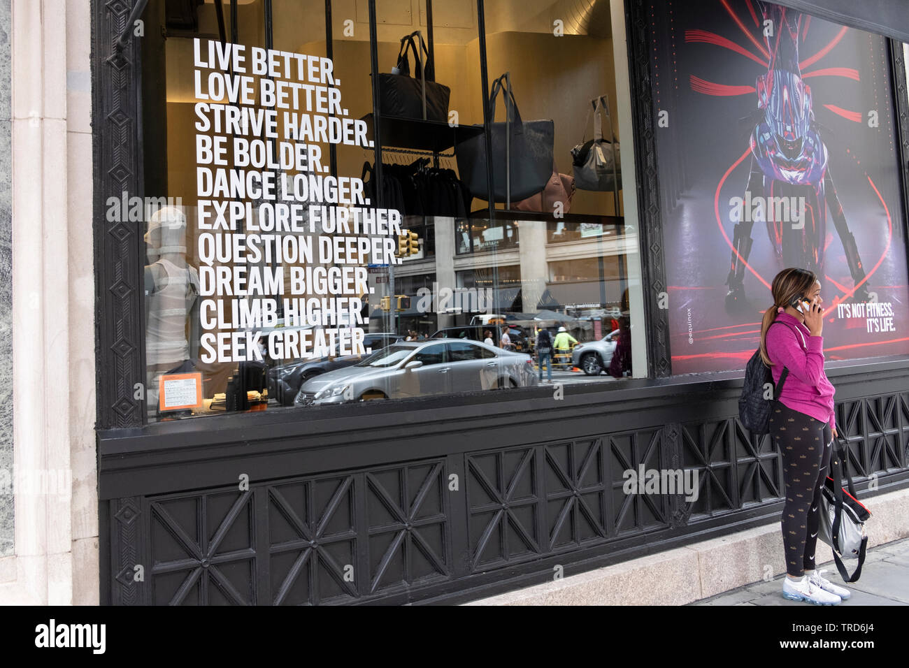Una mujer en el teléfono fuera de un gimnasio Equinox en Manhattan que tiene un mensaje más inspiradoras en su ventana. Imagen De Stock