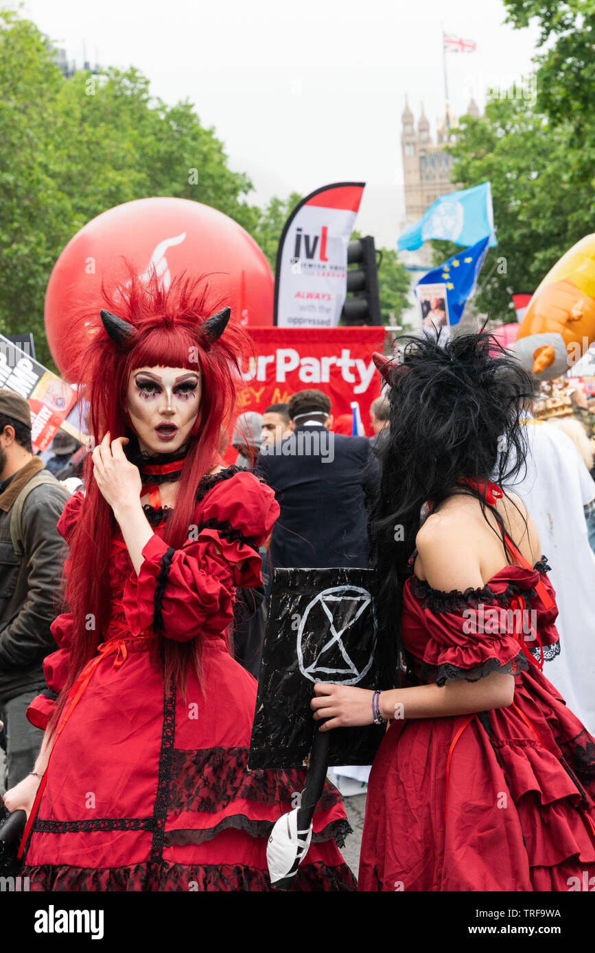 El 4 de junio de 2019. Londres, Reino Unido. Anti Trump rally en Westminster. Una mujer en traje de diablo sostiene extinción Rebelion pancarta a Trump protesta. Foto de stock