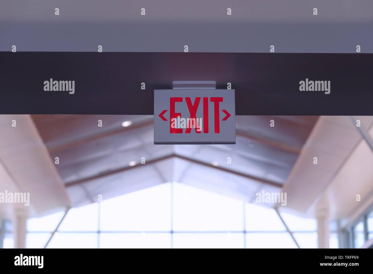 Señal de salida. Rojo fuego escapar cartel colgado en el techo en el aeropuerto. Foto de stock