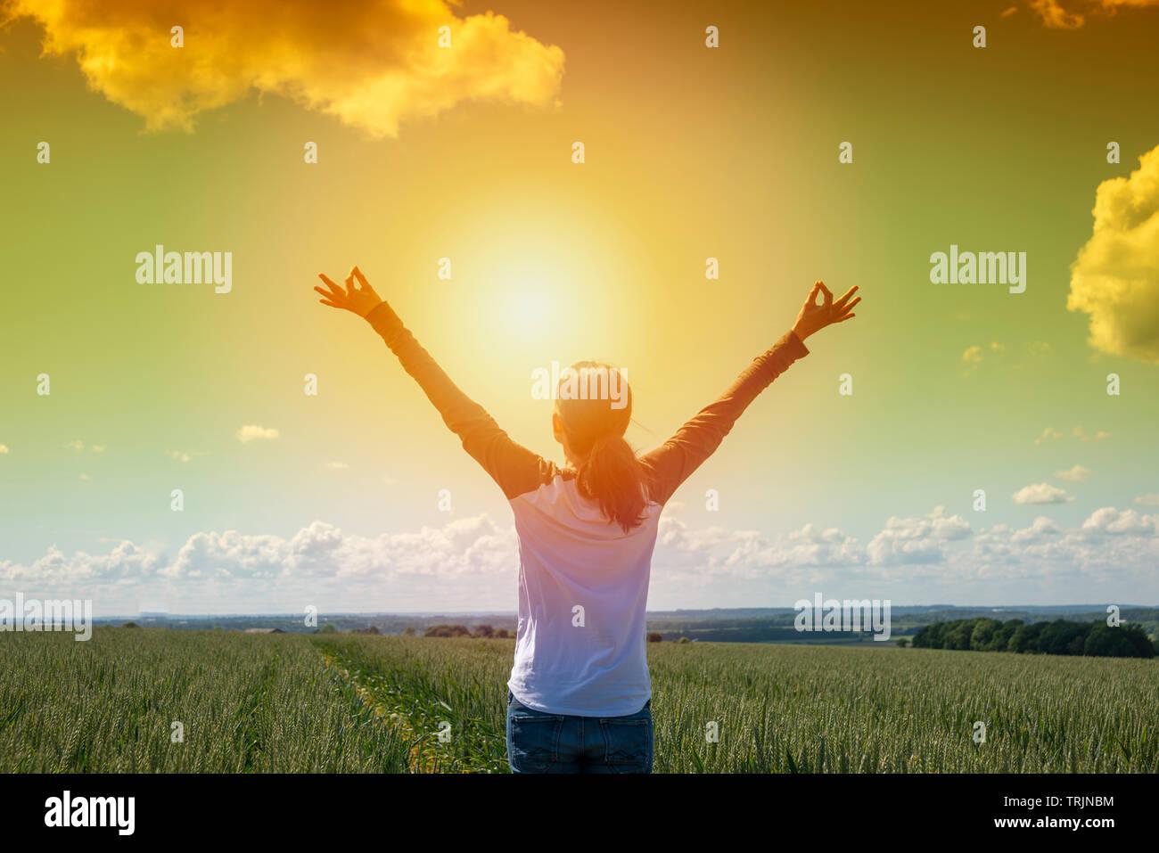 Vista posterior de una mujer al amanecer con sus brazos levantados en alegría y libertad de pie en un campo de trigo Foto de stock