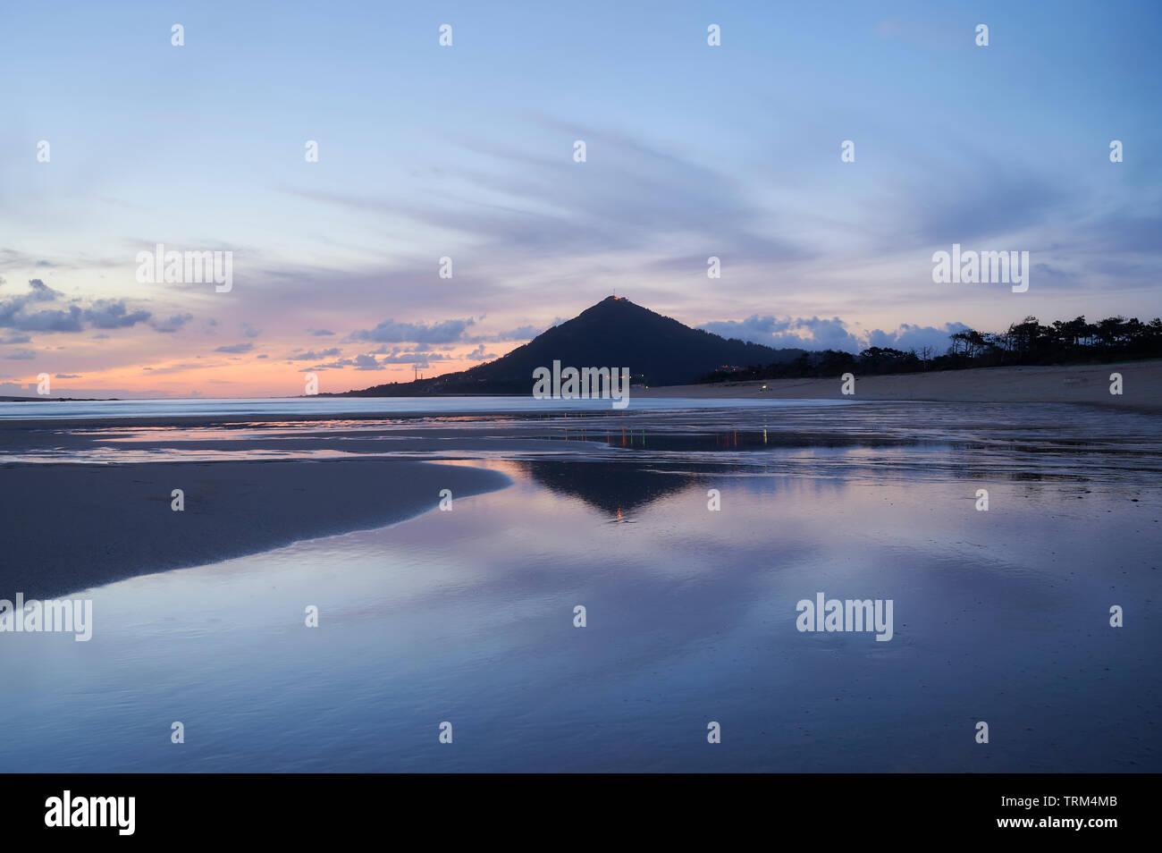 Playa de moledo al final del día, con miras a trega mountain en lado español de la frontera. Mostrar la marea baja y arenosa playa en un nublado da Foto de stock