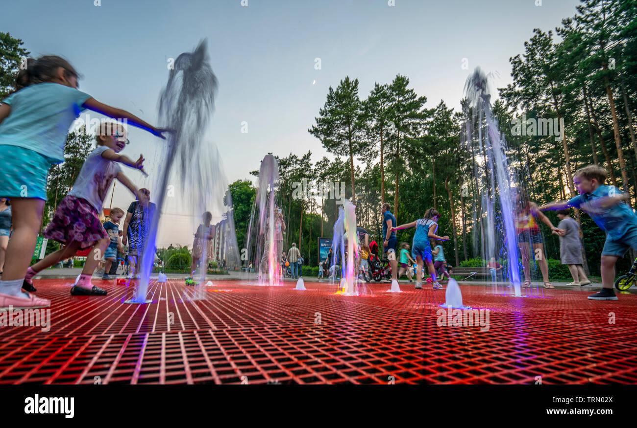 f30fdf026 Los niños en la ropa mojada jugando en la calle fontana al atardecer Imagen  De Stock
