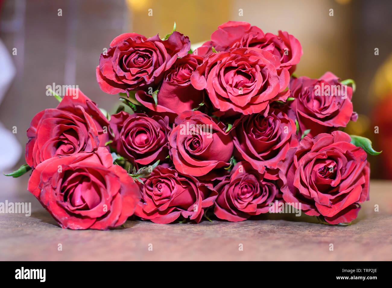 9b6df9a8dd4 Un ramo de rosas rojas brillantes acostado sobre una mesa de madera closeup  Imagen De Stock