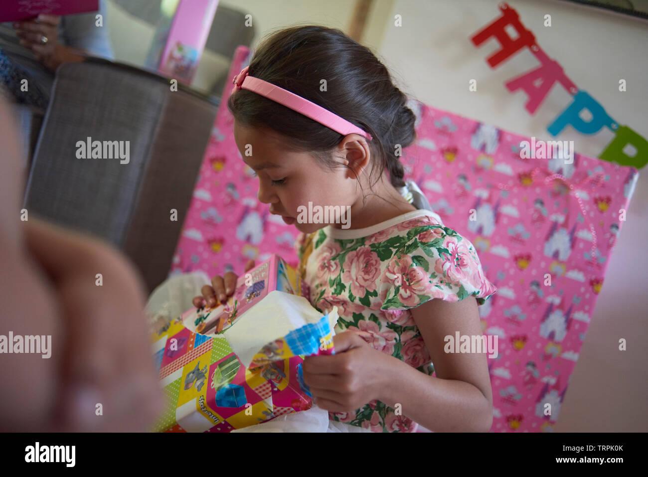 Linda chica Asiática de raza mixta desenvolver sus muchos regalos de cumpleaños en casa en el salón rodeado de su familia Imagen De Stock