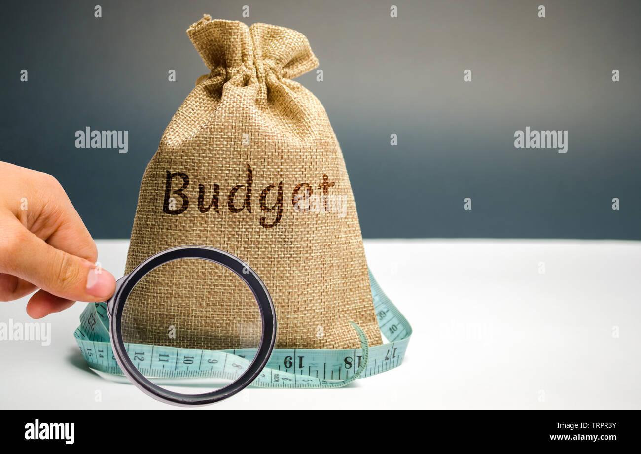 Bolsa de dinero con la palabra presupuesto y cinta métrica. El concepto de beneficio limitado. La falta de dinero y de la pobreza. Los pequeños ingresos. La reducción de los salarios. Unsuccessfu Foto de stock