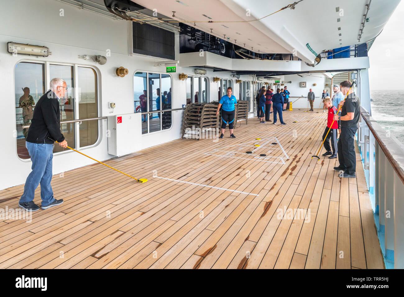 Los pasajeros jugando al tejo en la cubierta del barco crucero TUI Marella Explorer, Mar del Norte, Europa Imagen De Stock