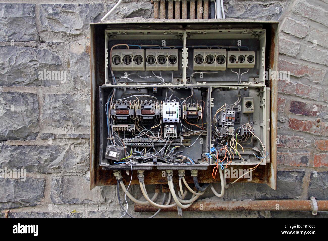 Caos de cables en una caja de fusibles en un edificio abandonado Foto de stock