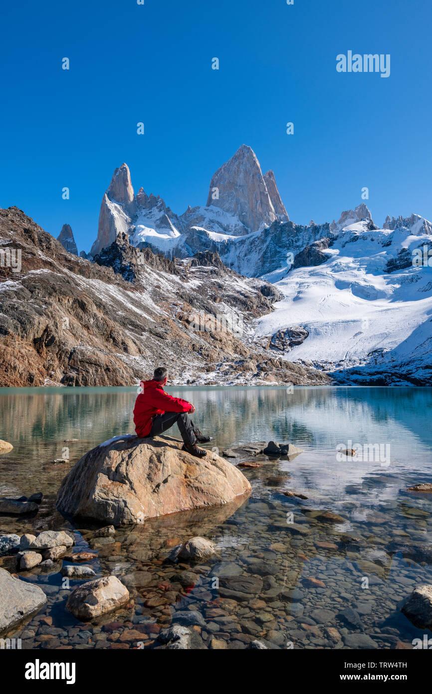 Un caminador sat admirando las vistas del Monte Fitz Roy y el Cerro Torre con lago de los Tres, El Chaltén, Patagonia, Argentina. Foto de stock