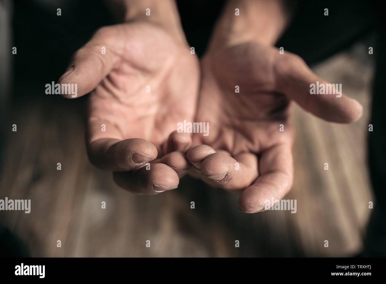 Varón mendigo manos para buscar dinero, monedas de bondad humana sobre el piso de madera en una calle o camino público de pasarela. Pobres sin hogar en la ciudad. Problemas con las finanzas, el lugar de residencia. Foto de stock