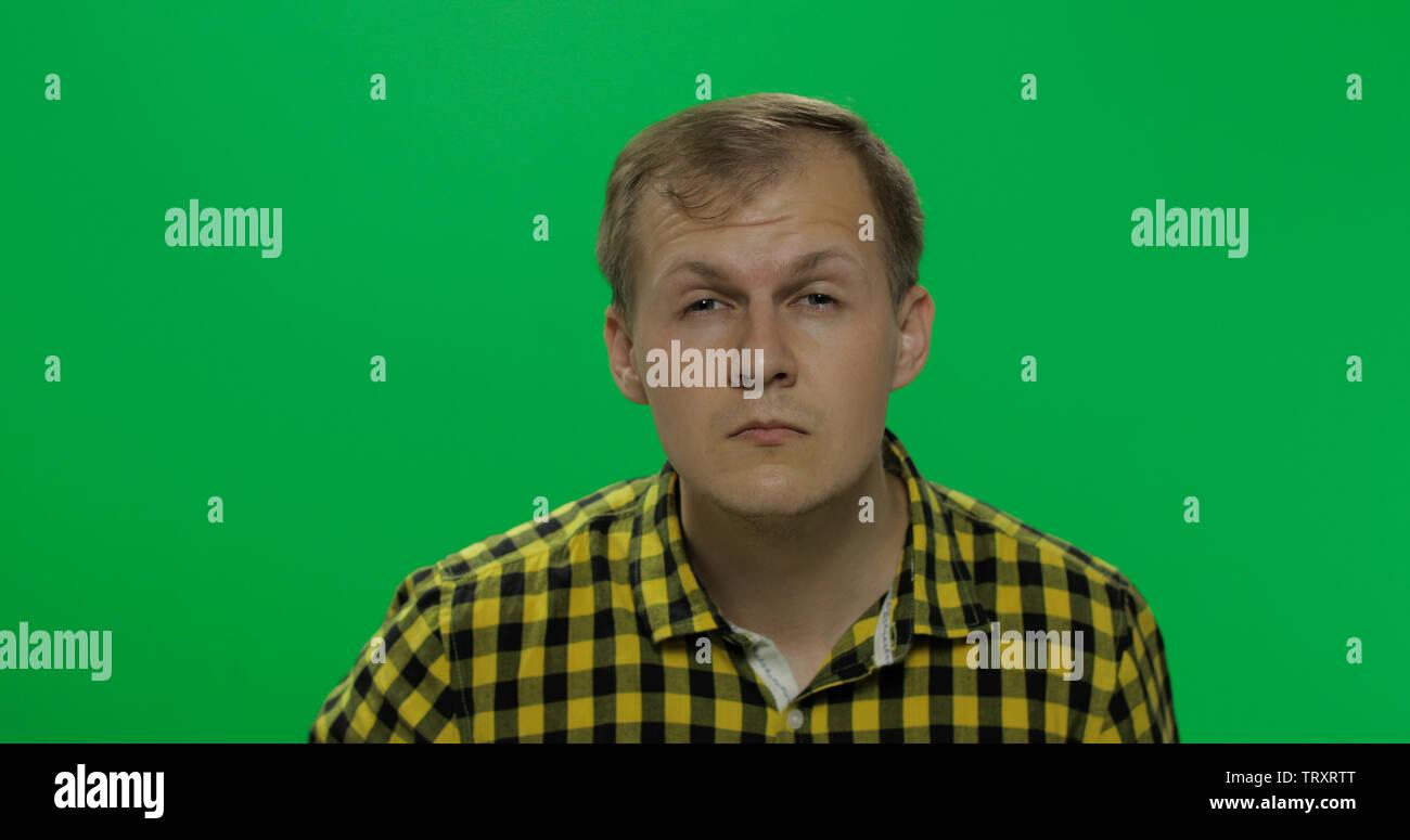 9690aa93d9 Apuesto joven en la camiseta amarilla sin gafas ve mal en el chroma key de  fondo