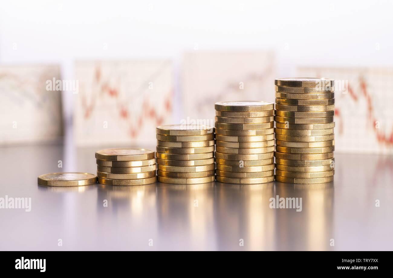 Aumento de los montones de monedas y gráficos con los precios de las acciones en el fondo mundial de uso | Foto de stock