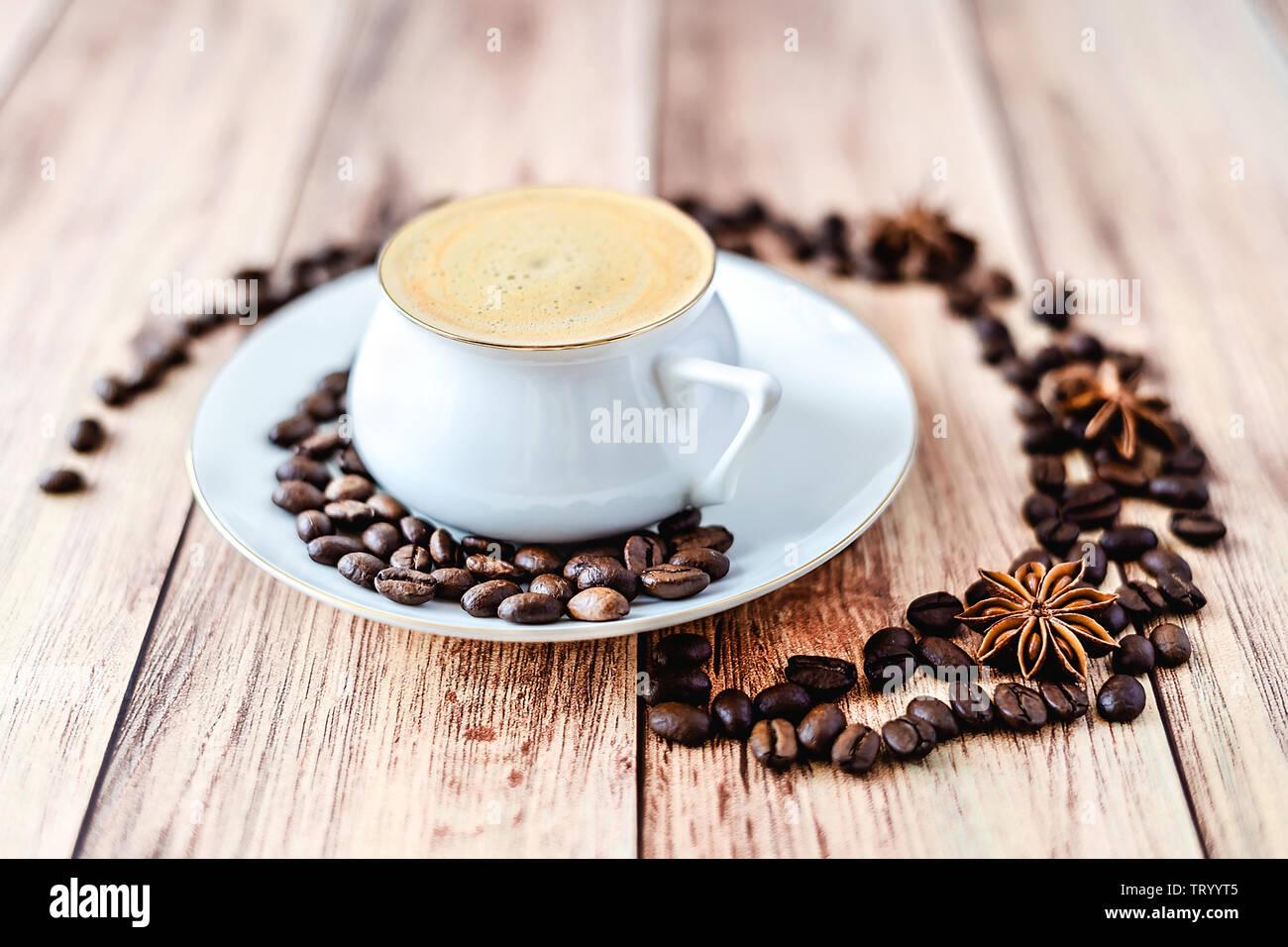 Vista cercana de una taza de café caliente sobre la mesa rústica de madera con granos de café derramado y anís. Espacio para el texto . Foto de stock