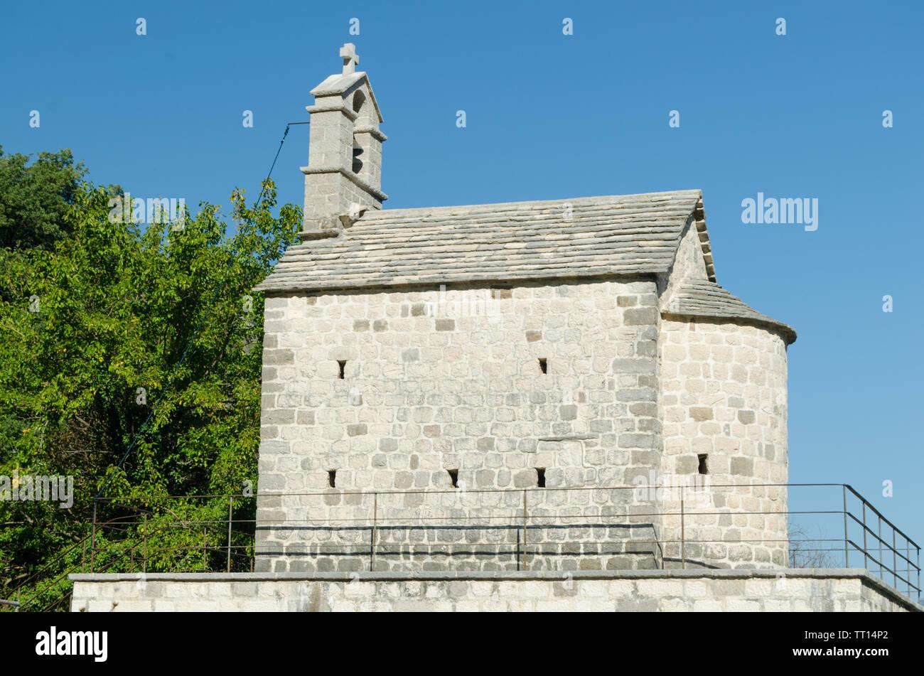Antigua Iglesia con un campanario entre árboles verdes.Arquitectura y antigüedades. Foto de stock