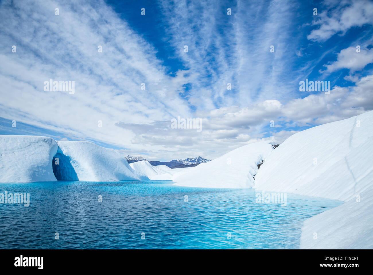 Cueva de hielo inundado por el azul profundo del Glaciar Matanuska pool en el glaciar, Alaska. El lago lleno en la cueva de hielo como el agua procedente de la fusión glaciar flo Foto de stock
