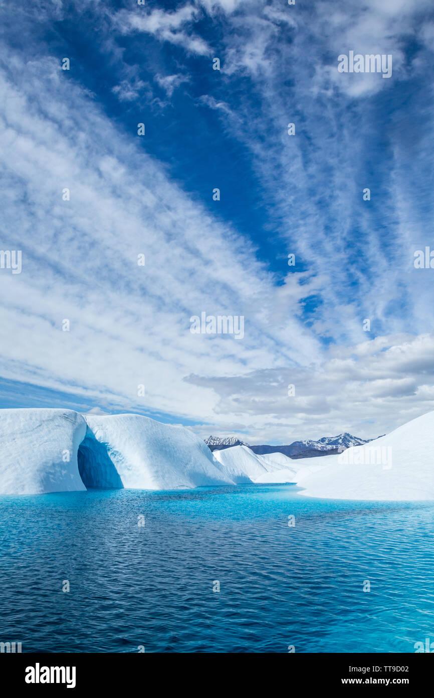 Las bandas de nubes de luz pasa sobre un lago de color azul profundo en el hielo del Glaciar Matanuska en Alaska. Una cueva de hielo también es visible en la parte izquierda, suelo Foto de stock