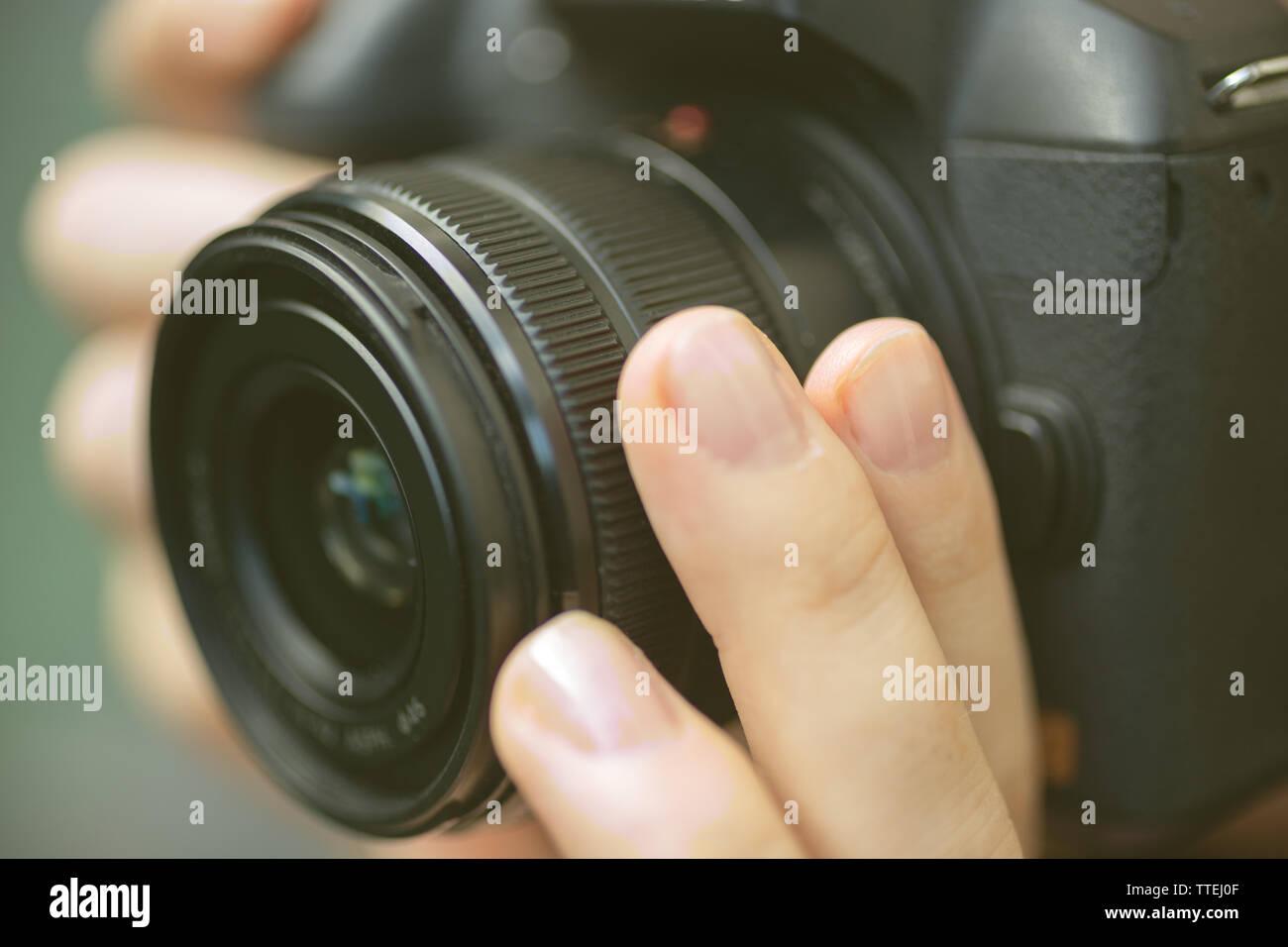 Fotógrafo manos sosteniendo una cámara digital, centrándose y tomando fotos, macro closeup Foto de stock