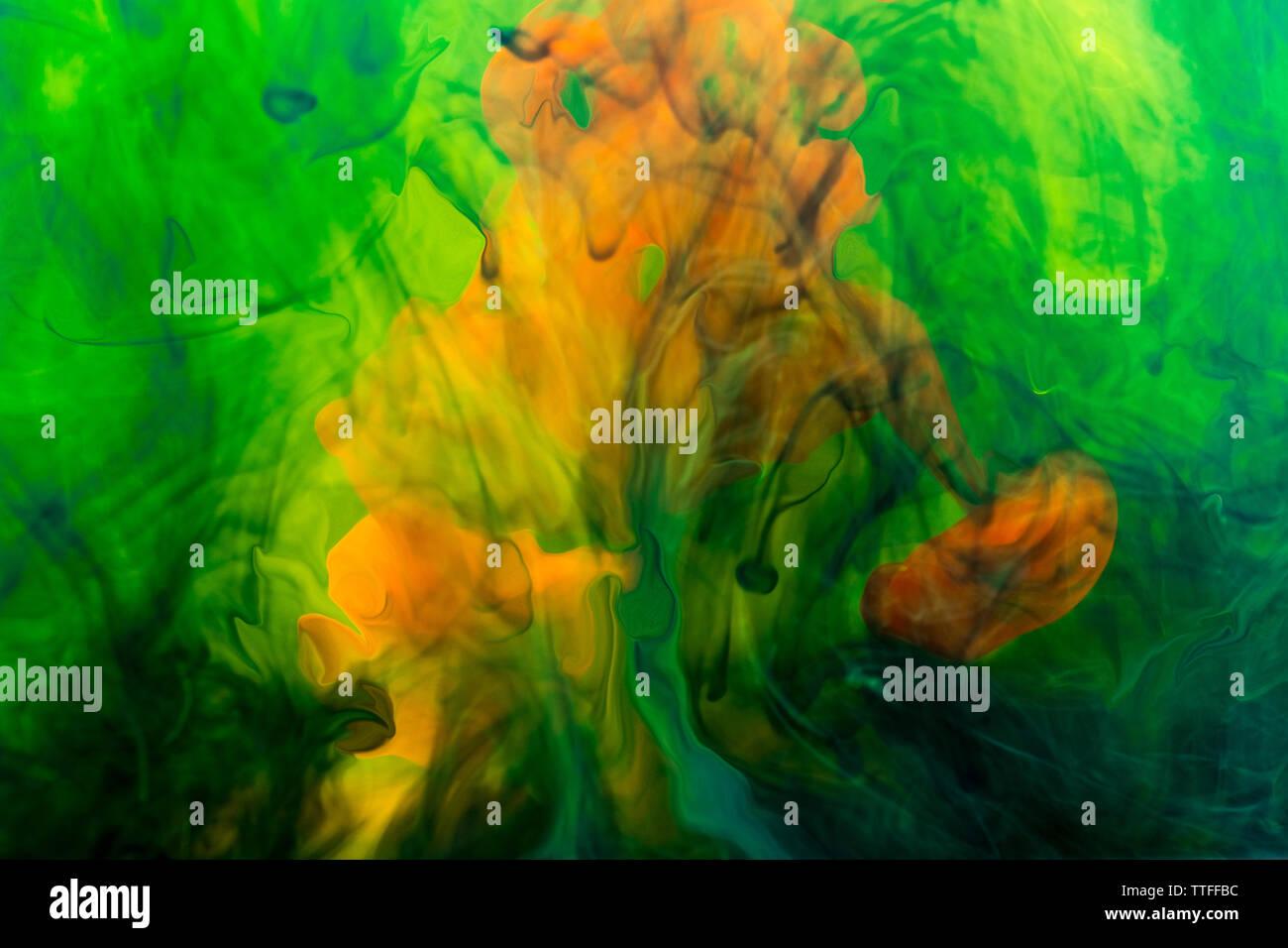 Tinta de color naranja y colores marinos disuelto en líquido. Imagen De Stock