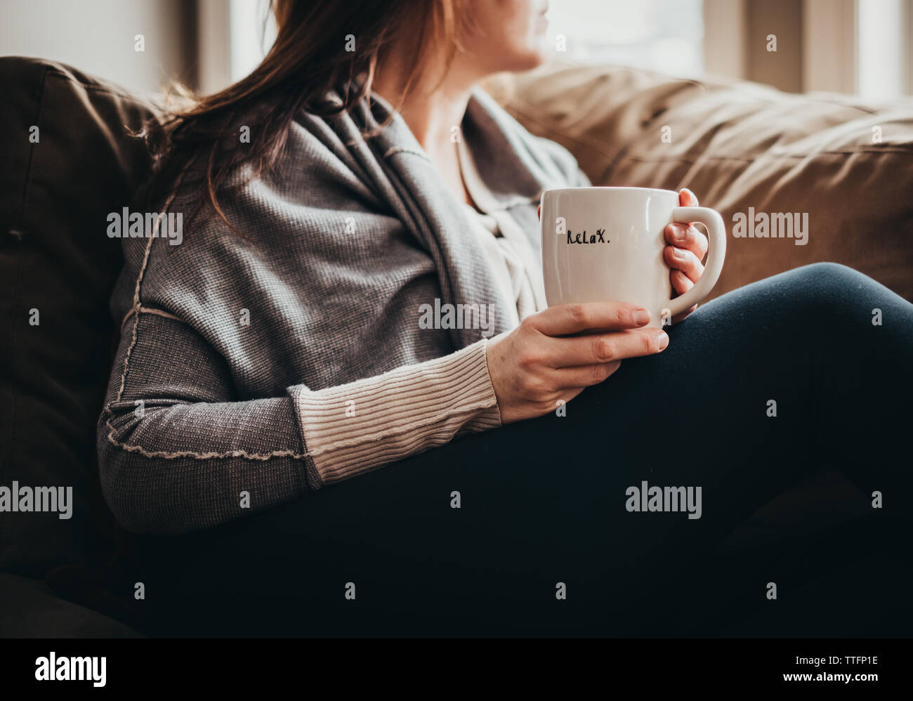 Imagen recortada de la mujer sosteniendo la taza con word relájese en un sofá. Foto de stock