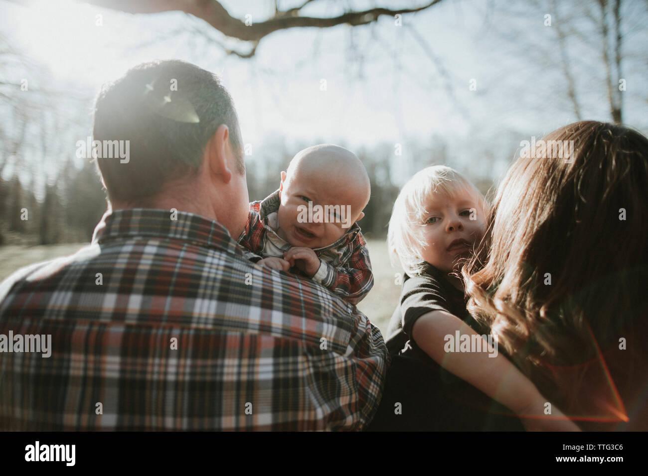 Bebés e Infantes mirar sobre el hombro de sus padres. Foto de stock