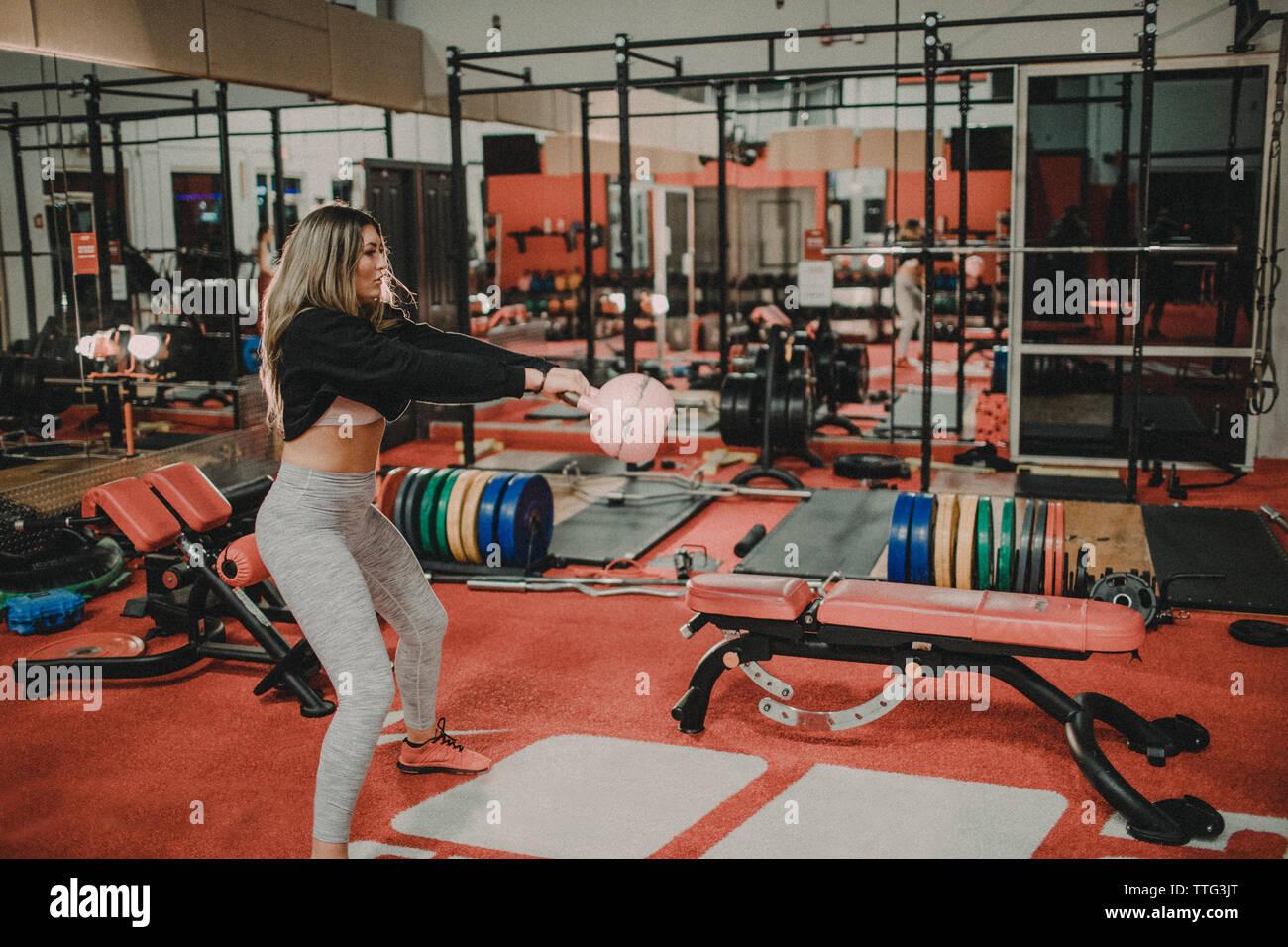 Colocar mujer ejerciendo con rosa kettlebell en el gimnasio. Imagen De Stock