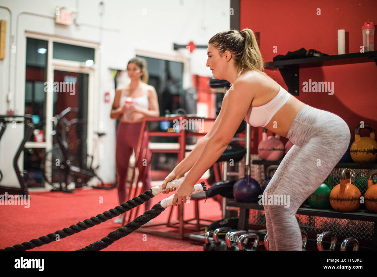 Colocar mujer intensa batalla cuerda haciendo ejercicio en el gimnasio. Imagen De Stock