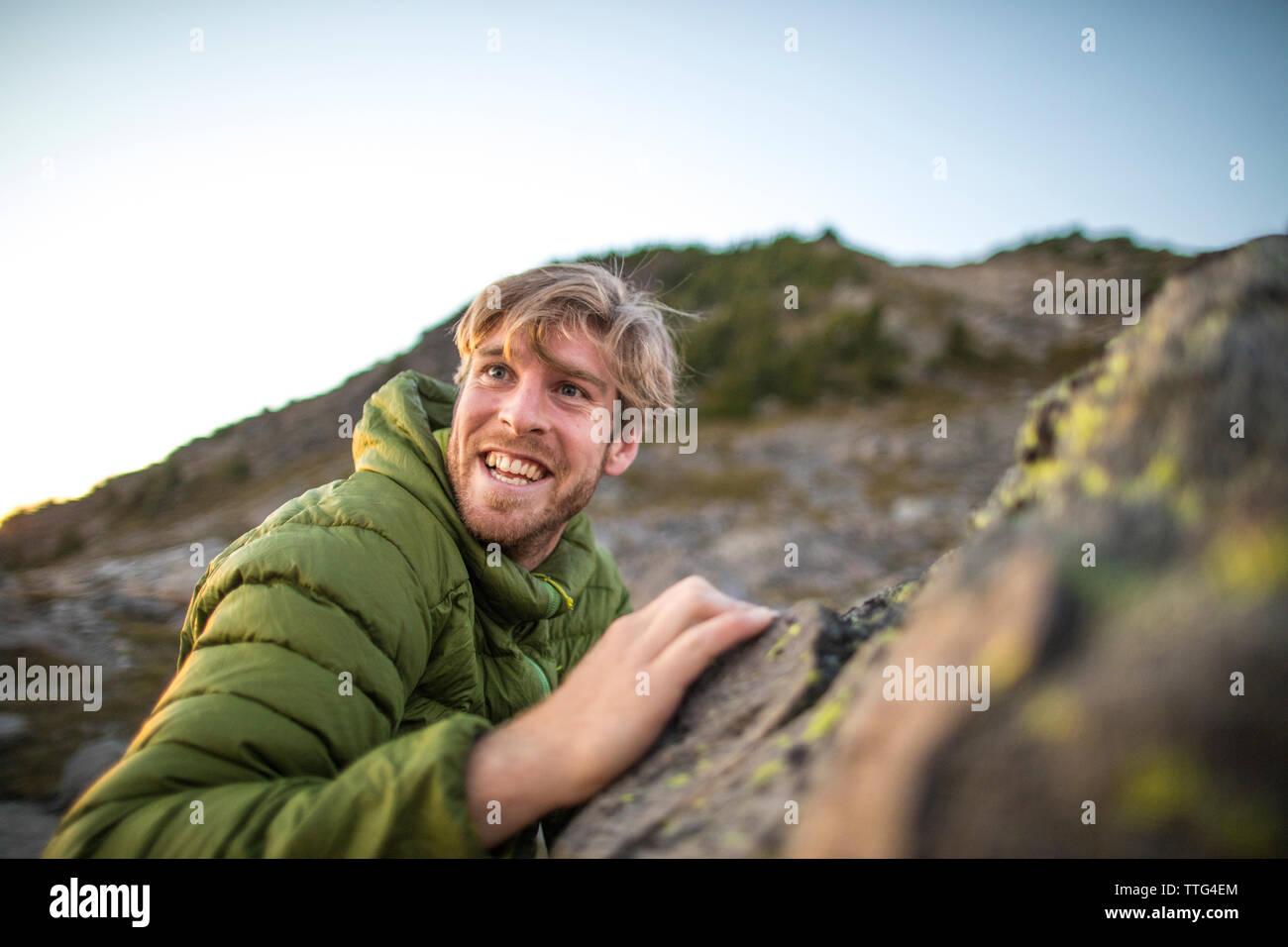 Vista lateral del hombre feliz la escalada en roca. Foto de stock