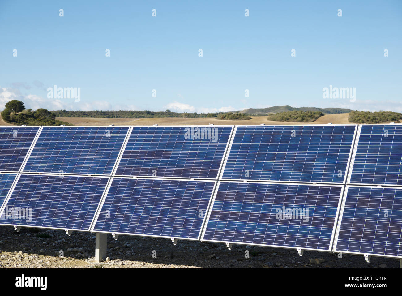 Paneles solares en el paisaje contra el cielo azul durante el día soleado Imagen De Stock