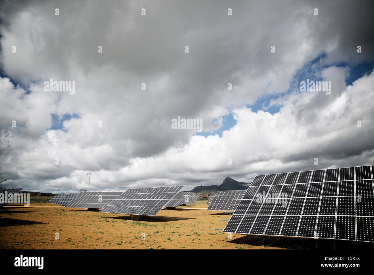 Paneles solares en el paisaje contra el cielo nublado Imagen De Stock
