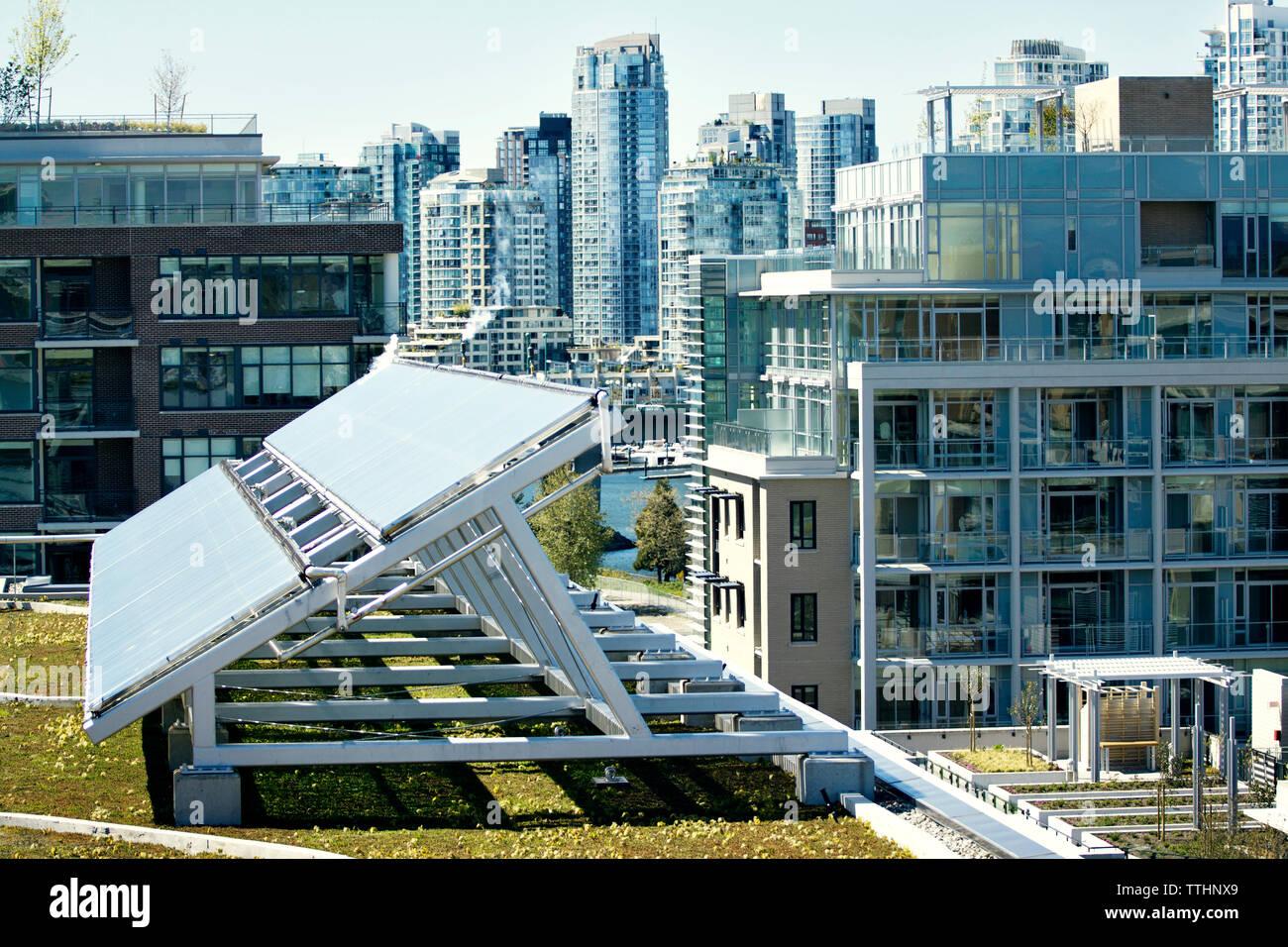 Panel solar en el campo de edificios en la ciudad Foto de stock