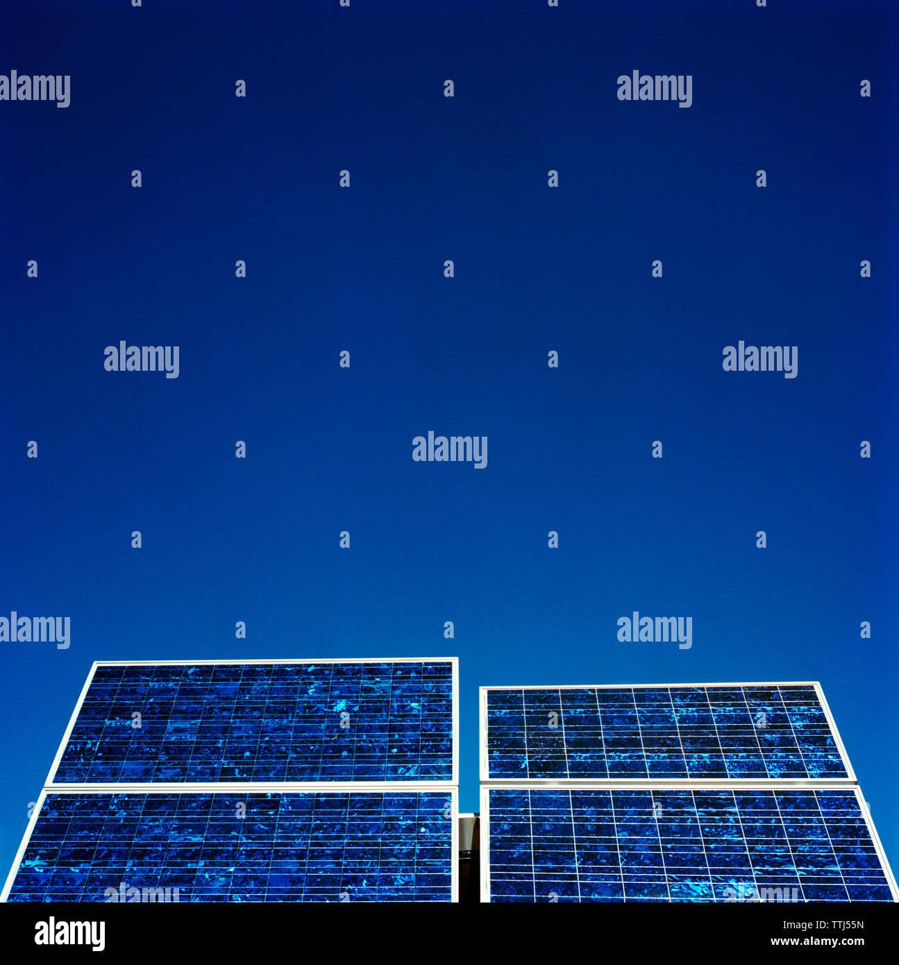 Ángulo de visión baja de paneles solares contra el cielo azul claro Imagen De Stock