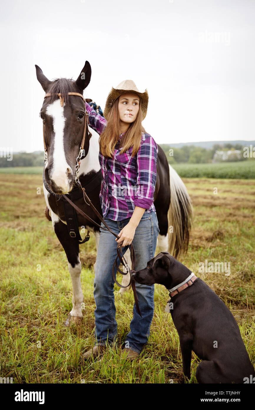 Mujer con caballo y perro mirando lejos estando de pie en el campo Foto de stock