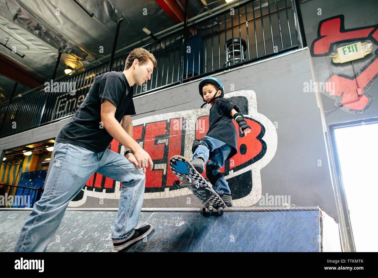 Joven se prepara para caer en una rampa de skate con ayuda del instructor Foto de stock
