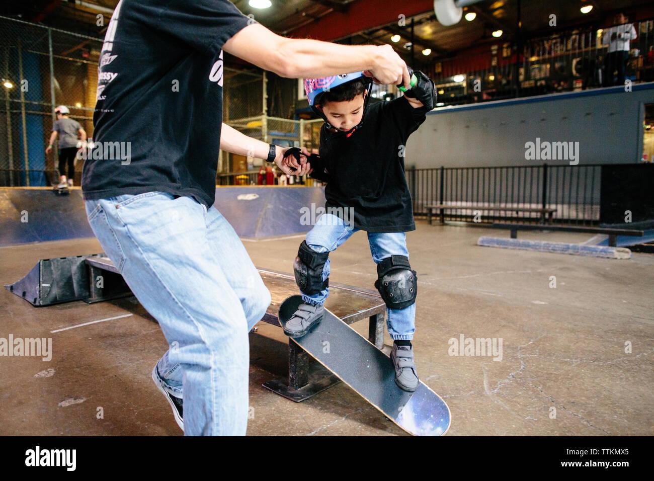 Joven toma un salto con la patineta mientras mantiene las manos del maestro Foto de stock