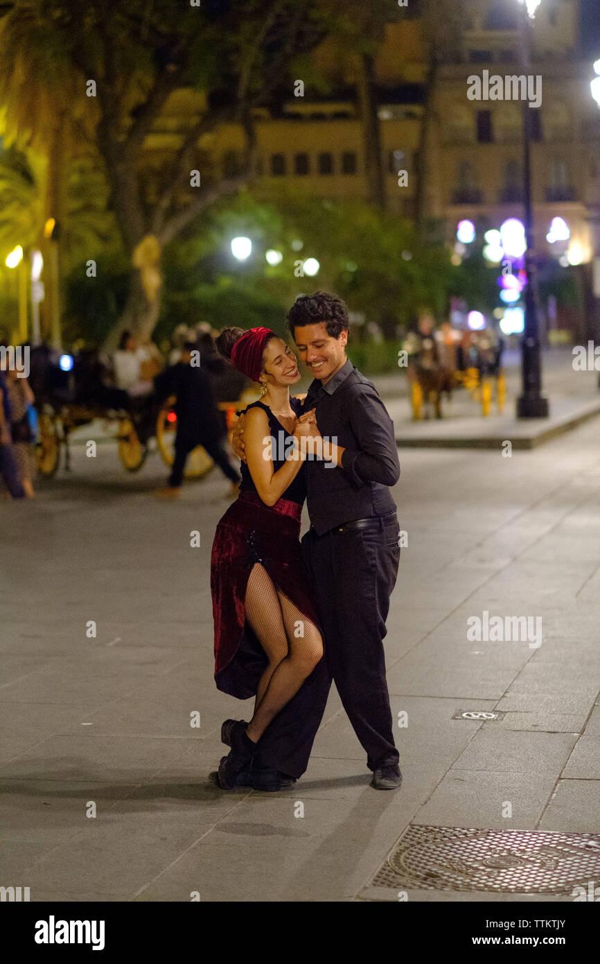 Un baile de pareja en las calles de Sevilla Foto de stock