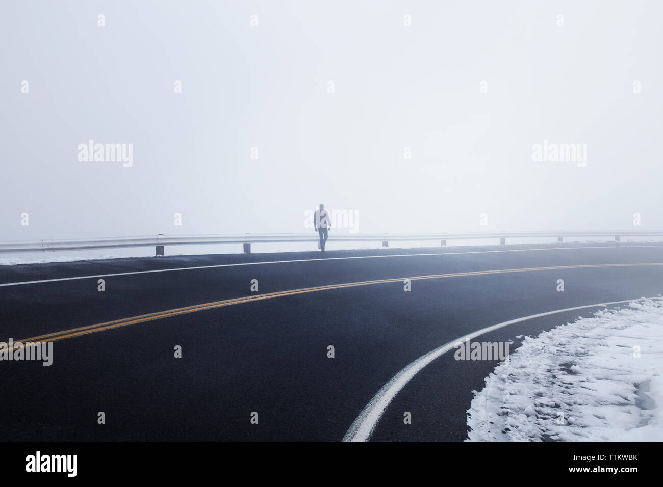 Hombre caminando por la autopista durante la niebla Foto de stock