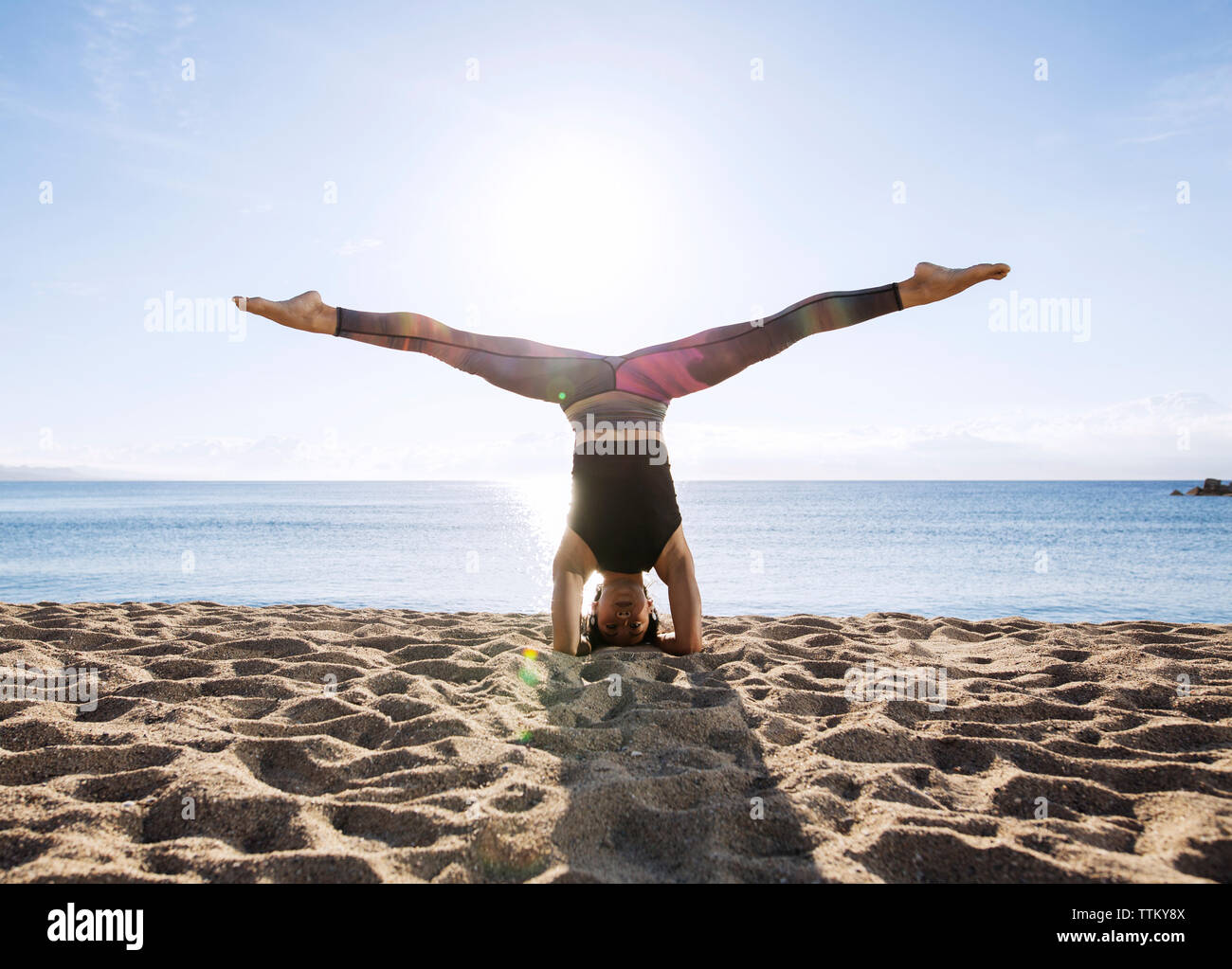 Mujer joven con piernas separadas realizar hacer el pino en la playa Imagen De Stock