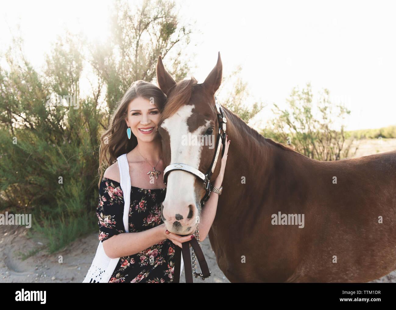 Retrato de una mujer sonriente con un caballo parado sobre el campo contra el cielo despejado Foto de stock