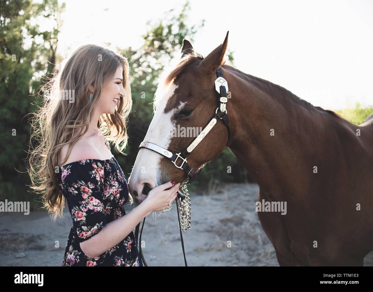 Vista lateral de la mujer sonriente acariciando el caballo mientras se encuentra en el campo contra el cielo despejado Foto de stock