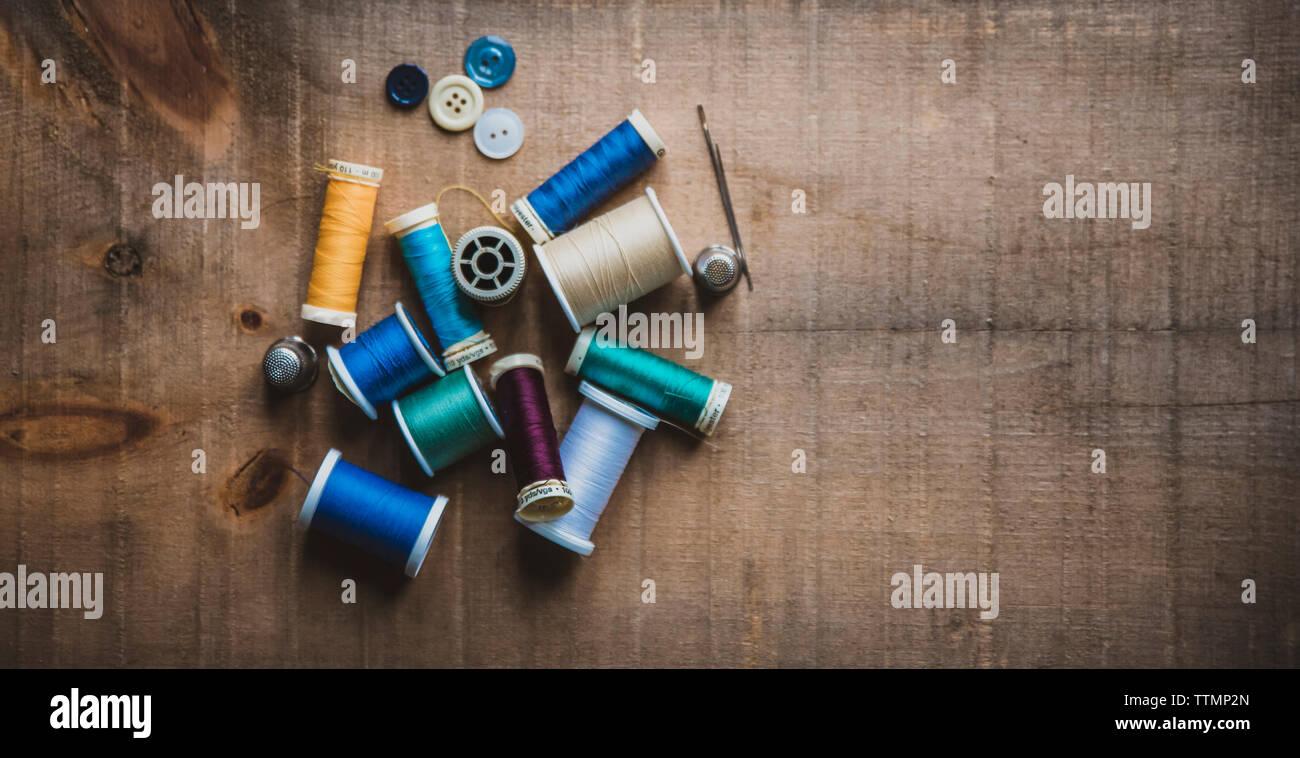 Alta Vista angular de carretes coloridos con dedales y botones en la mesa de madera en el taller Foto de stock
