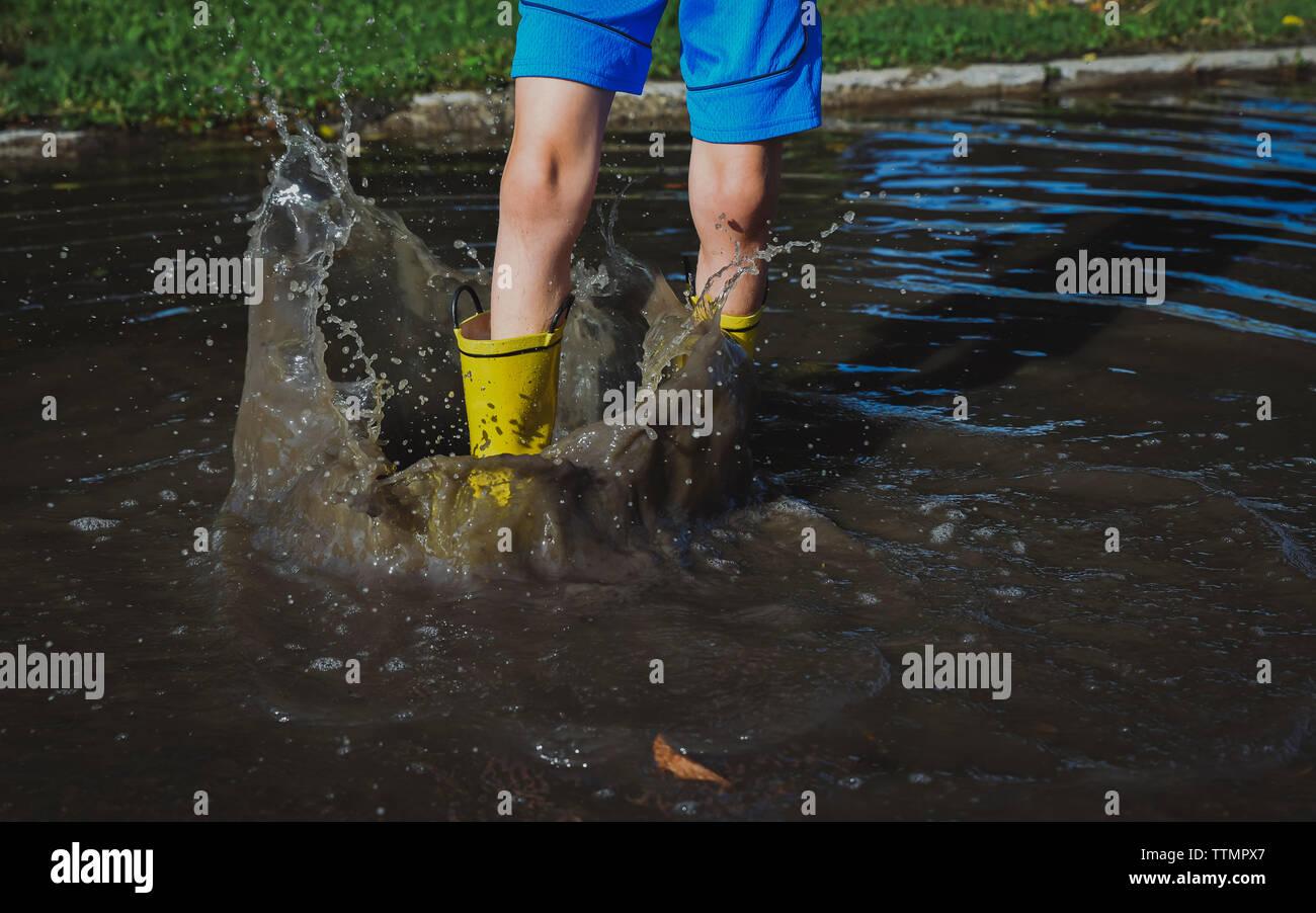 Bajo la sección de estampación muchacho juguetón pie mientras está parado en el charco en park Foto de stock