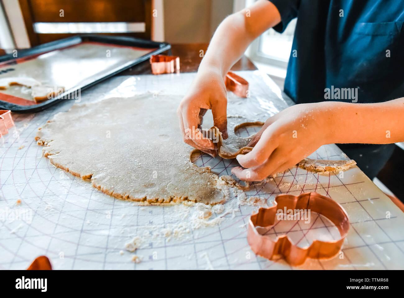 Cerca de las manos del niño hacer galletas con cortadores para galletas. Foto de stock