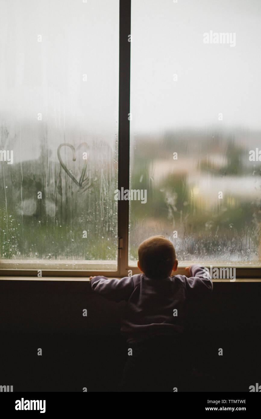 Una niña mirando a través de una ventana cubierta con el vapor y el corazón Foto de stock