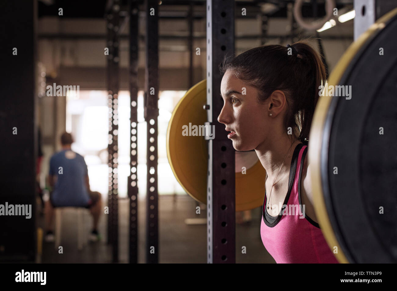 Elevación de la atleta femenina determinada barbell en club de salud Foto de stock