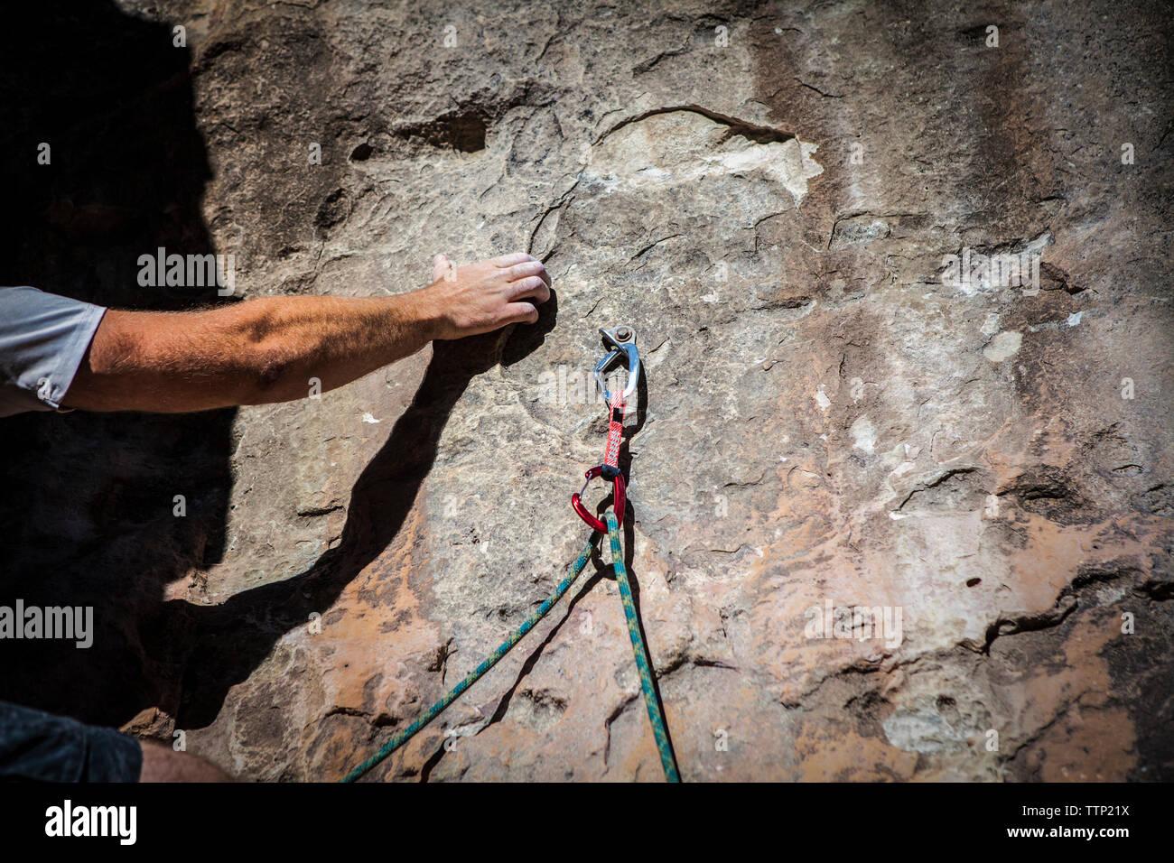 Imagen recortada de agarre de mano, mientras que la escalada en roca Imagen De Stock