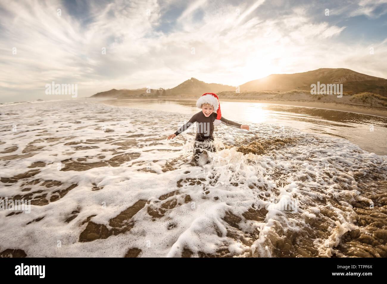 Felices vacaciones niño usando hat jugando en el agua en una playa Foto de stock
