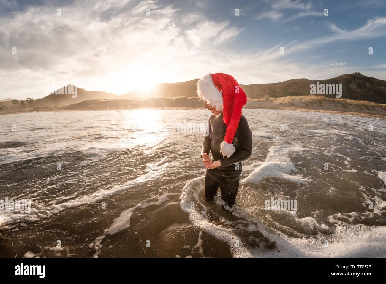 Niño feliz vestidos de rojo Santa hat parado en agua en la playa al anochecer Foto de stock